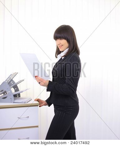 Beautiful business women reading documents at her office