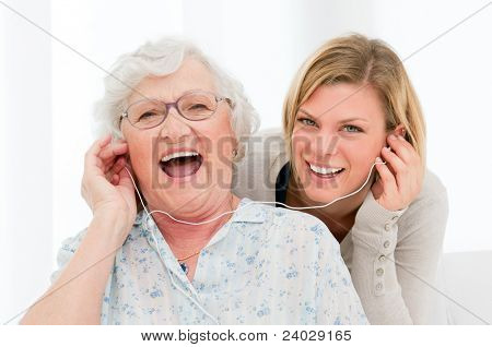 Super happy and excited grandmother listening music with her granddaughter at home