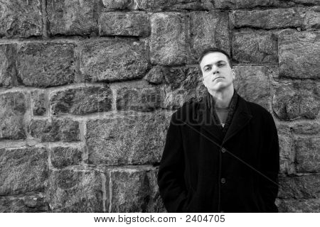 Man Leans Against Stone Wall