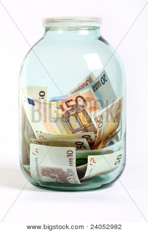 Glass money jar of Euro banknotes