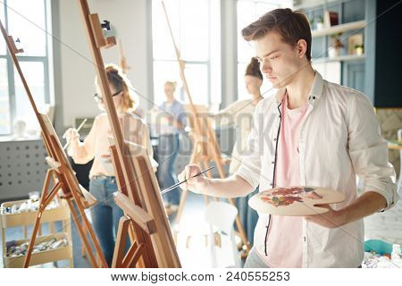poster of Serious guy concentrating on his painting on easel during lesson in school of arts