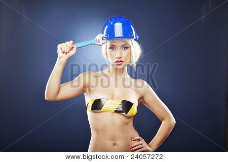 Blonde Girl With Construction Helmet And Adjustable Wrench.