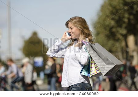 woman on urban street with shopping bags and cellphone