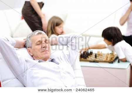 Relaxed senior man on sofa taking a nap, family in background