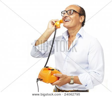 portrait of middle aged man talking using a vintage telephone over white background