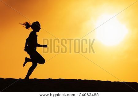 Girl silhouette running over sunset sky. Copyspace.