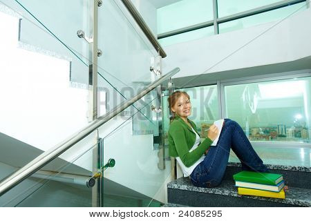 Image of pretty girl with books looking at camera on steps of college
