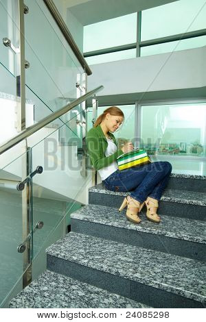 Portrait of pretty girl sitting on stairs and making notes in copybook