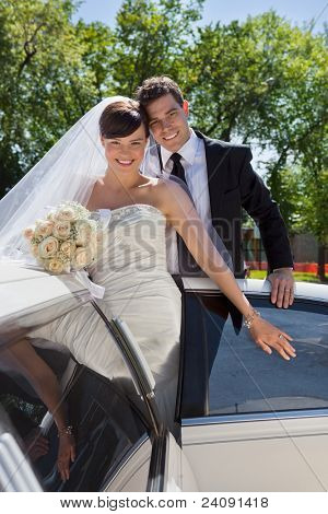 Happy newly wed couple getting in the car