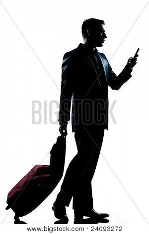 one caucasian business traveler man walking with telephone and  suitcase  full length silhouette in studio isolated white background