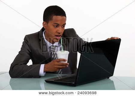 young Afro-American businessman looking at his laptop and drinking his coffee