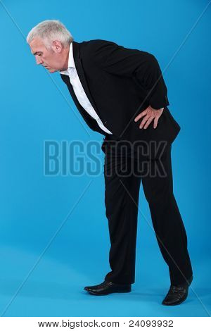 Man bending over to look at something on the floor