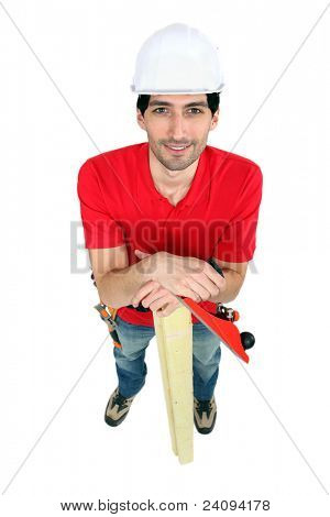 craftsman holding a board and a rasp