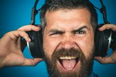 Emotional Man With Headphones Listening Music. Closeup Portrait. Stylish Happy Man Listening To Musi poster