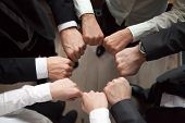 Business Team Or Partners Put Fists In Circle As Concept Of Motivating Engaging Teambuilding Activit poster