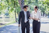 Businessman And Businesswoman Talking Outdoors About Their Business With Tablet And Walking Through poster