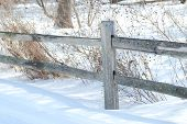stock photo of split rail fence  - A gray split rail wooden fence in a snowy country winter landscape - JPG