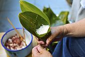 Chinese Making Zongzi, Traditional Chinese Rice Dumplings For Dragon Boat Festivals. Hand Holding Le poster
