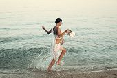 Young Beautiful Lady Run On Sea Or Ocean Beach In Water Splash. Freedom Concept. Woman Carries Shoes poster