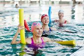 Smiling mature female in swimwear and two more active women listening to trainer advice during gymna poster