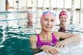 Healthy mature sportswoman and her friends in swimwear spending time in swimming-pool poster