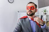 Happy Super Businessman In Mask And Cape Looking Away In Office poster