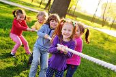 A Group Of Small Preschool Children Play A Tug Of War In The Park. poster