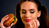 Woman eating hamburger. Girl wants to eat burger. Student consume fast food. Portrait of person with poster