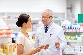 medicine, healthcare and people concept - female customer giving prescription to senior apothecary a poster