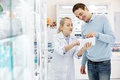 Special Prescription Drug. Professional Female Pharmacist Using Tablet While Communicating With Man poster