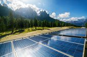 Solar Cell Panel In Country Landscape Against Sunny Sky And Mountain Backgrounds. Solar Power Is The poster