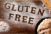 high-angle shot of a wooden table sprinkled with a gluten free flour where you can read the text glu poster