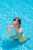 Naughty Little Boy Filling His Water Gun In Swimming Pool poster