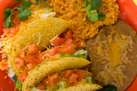 image of mexican food  - A plate of sterotypical Mexican food including tacos bean rice cilantro and a green jalapeno pepper - JPG