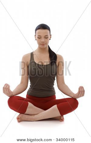 Young girl practicing yoga, sitting in tailor seat, relaxing eyes closed.