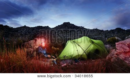 Tent camping wilderness adventure man with headlamp and gas burner in the mountains cooking food at night while looking into panorama of the great outdoors