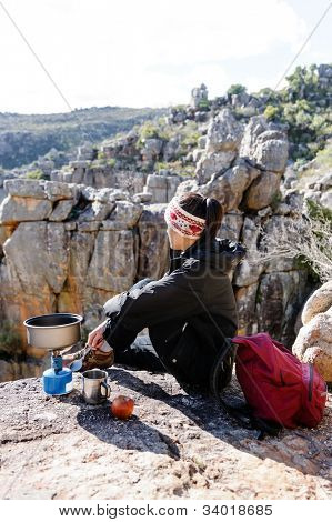 Chinese asian woman sitting and enjoying the view after a hike, trek in the mountains on an adventure tourism holiday camping trip