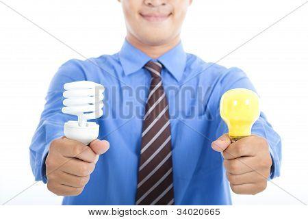 Smiling Businessman holding energiesparende Glühbirne und Tradition-Glühbirne