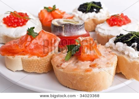 group of small sandwiches with red and black caviar, herring  and salmon