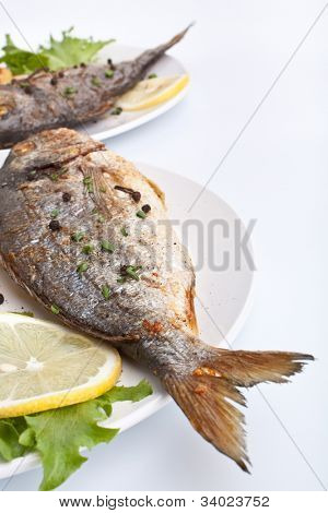 two servings of Sea Bream fish with lemon on white plate
