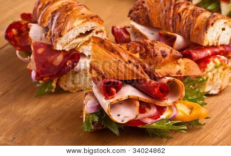 three tasty meat, cheese  and vegetables sandwiches
