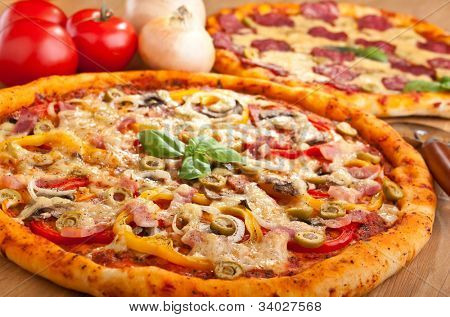 ham, mushroom and vegetable pizza and salami pizza at the back