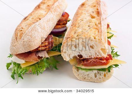 two halves of long white wheat baguette sandwich