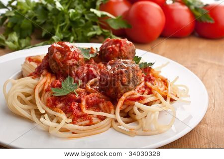 Plate Of Spaghetti With Meatballs In Tomato Marinara Sauce And Ingredients On A Wooden Table