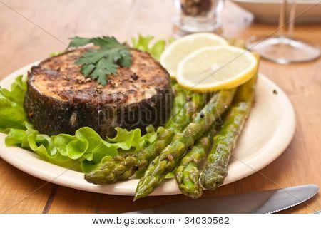 serving of spicy  broiled halibut garnished with asparagus and lemon