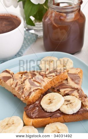 chocolate and peanut buttered toasts with pieces of bananas on a plate, an open chocolate spread container and  a cup of hot chocolate