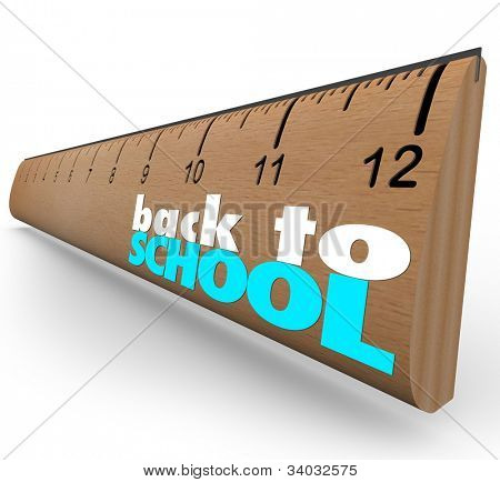 The words Back to School on a wooden ruler to measure or illustrate the message that  break is over and it's time to return to the classroom and continue your education and lessons