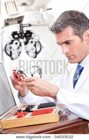 Optometrist looking at measuring eye glasses.