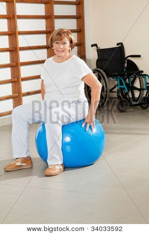 Full length portrait of a happy senior woman sitting on fitness ball at hospital gym
