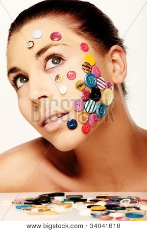 Beautiful woman with creative flair wearing a diverse selection of colourful buttons adhering to her cheek